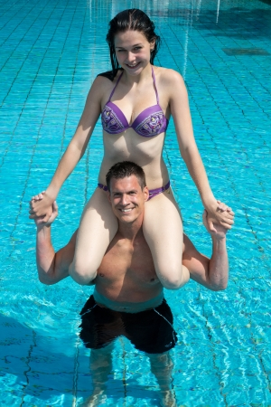 Couple having fun in the water at public swimming pool. She is sitting on his shoulder photo