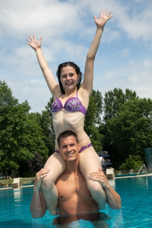 Couple having fun in the water at public swimming pool. She is sitting on his shoulder 版權商用圖片