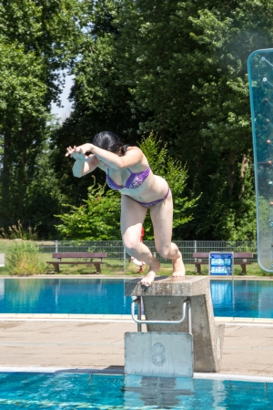 Girl jumping from starting block at public swimming pool photo