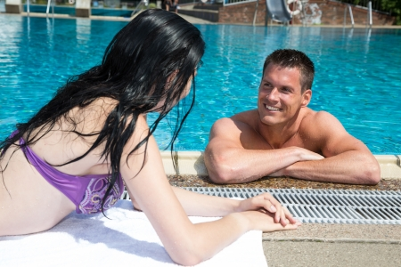 Couple flirting with each other at the pool edge photo