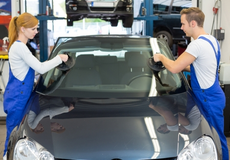 Mechanics or glaziers install windshield or windscreen for replacement in garage photo