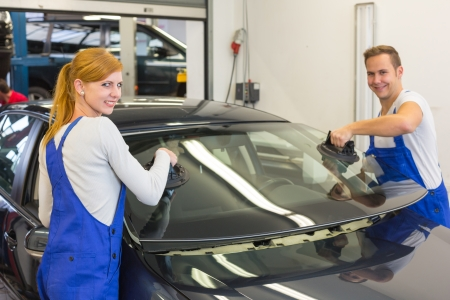 Two glaziers replace windshield or windscreen on a car in workshop after stone-chipping