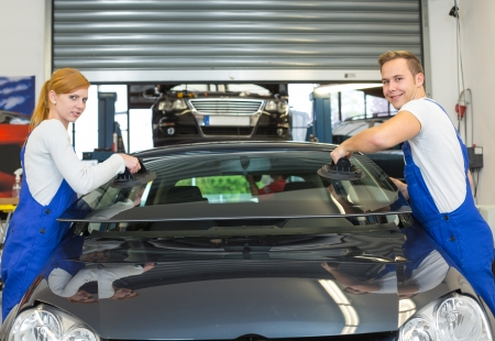 window repair: Two glaziers replace windshield or windscreen on a car in workshop after stone-chipping