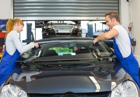 Mechanics or glaziers install windshield or windscreen for replacement in garage Stock Photo