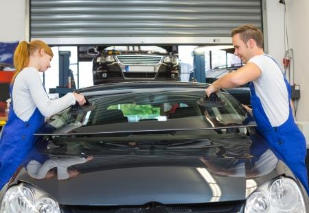 Mechanik oder Glaser installieren Windschutzscheibe oder Windschutzscheibe für den Austausch in der Garage