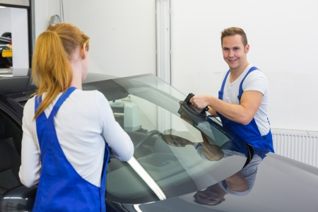 windscreen: Mechanics or glaziers install windshield or windscreen for replacement in garage Stock Photo