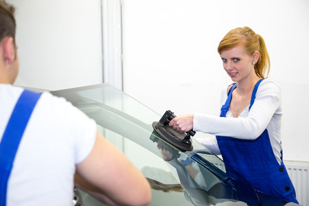replaces: Glazier replaces windshield or windscreen on a car in workshop garage