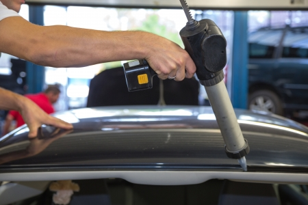 windscreen: Glazier with application gun applying adhesive for windshield or windscreen replacement after stone-chipping