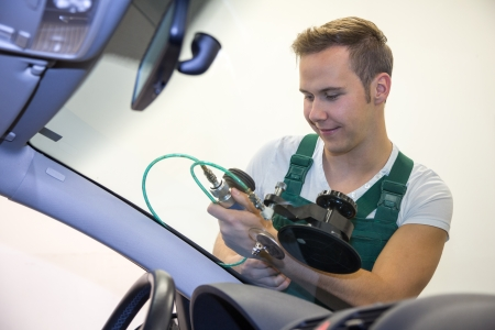 glazier: Glazier repairing stone-chipping damage on cars windshield or windscreen Stock Photo