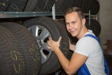 garage automobile: Mécanicien dans la roue ou pneu entrepôt d'un garage