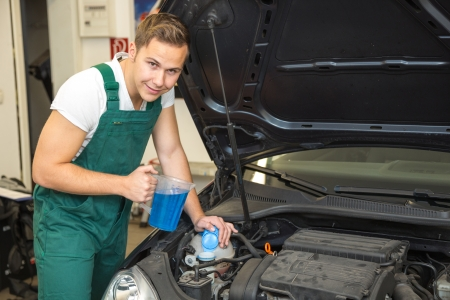 Mechanic refills coolant or cooling fluid in motor of a car photo