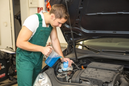 fluid: Mechanic refills coolant or cooling fluid in motor of a car