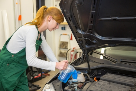 Female mechanic refills coolant or cooling fluid in motor of a car