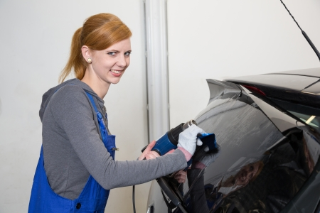 tinting: Female worker tinting car window in garage with a tinted foil or film
