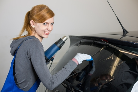tinted: Female worker tinting car window in garage with a tinted foil or film