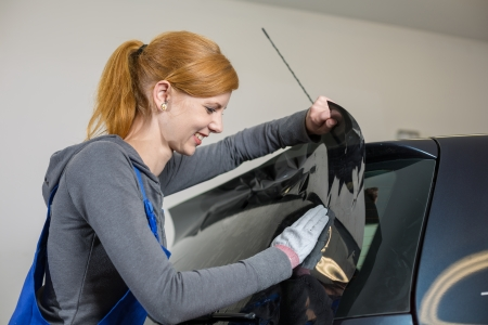tinting: Car wrappers tinting a vehicle window with a tinted foil or film using heat gun and squeegee