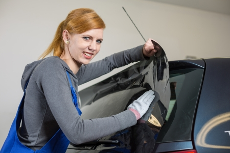 tinted: Car wrappers tinting a vehicle window with a tinted foil or film using heat gun and squeegee