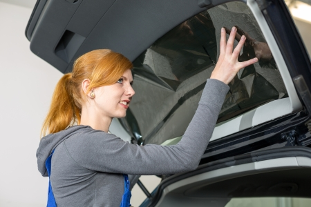 Worker in garage tinting a car window with tinted foil or film Standard-Bild