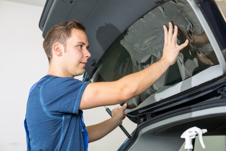 tint: Car wrappers tinting a vehicle window with a tinted foil or film using heat gun and squeegee
