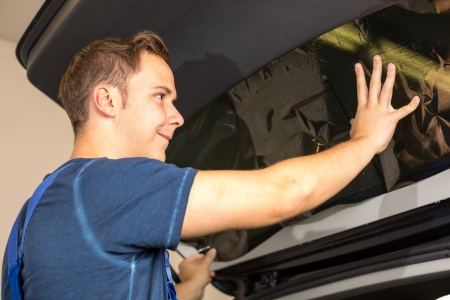 Worker in garage tinting a car window with tinted foil or film Stock Photo