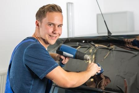 Car-Wrapper Tönen einer Fahrzeugscheibe mit einer getönten Folie oder Film mit Heißluftpistole und Rakel