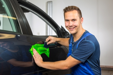 squeegee: car wrapping professional wrapping car door handle in colorful foil or film using a squeegee Stock Photo