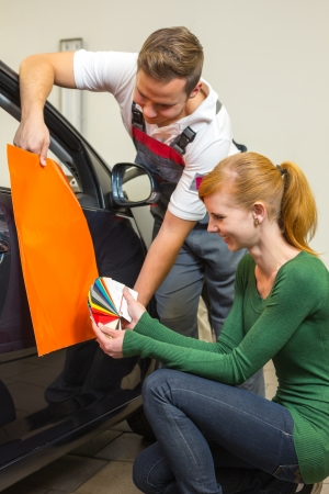 Car branding specialist consults a client about different types of adhesive foils or films for wrapping vehicles