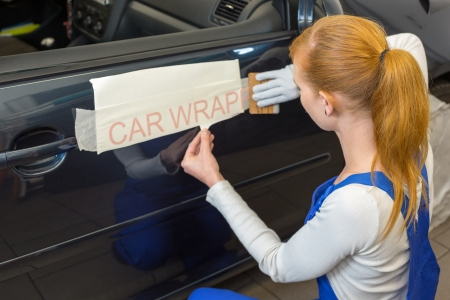 Car wrapping professional puts letters made of vinyl foil or film on vehicle door