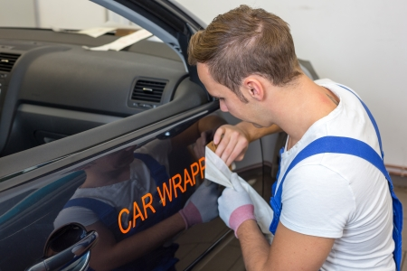 wrappings: Car branding specialist puts logo with car wrapping foil or film on vehicle door