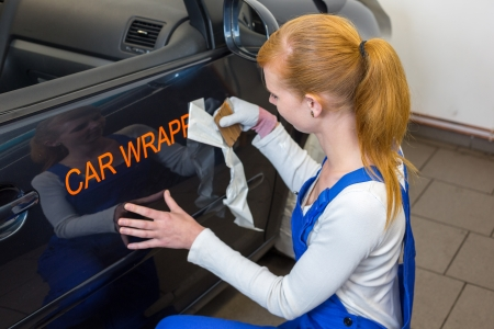 Car branding specialist puts logo with car wrapping foil or film on vehicle door