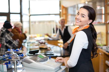 maquina registradora: Vendedora de trabajo en la caja registradora o la caja mostrador de la tienda