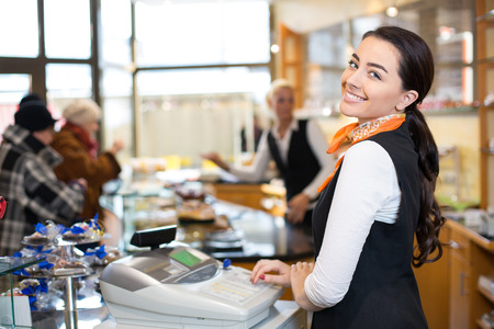 Saleswoman working at cash register or checkout counter in shop Standard-Bild