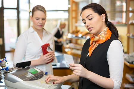 maquina registradora: Cliente en la tienda de pagar en la caja registradora con la vendedora
