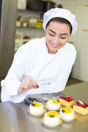 Konditor bereitet Kuchen in der Bäckerei oder Konditorei Lizenzfreie Bilder