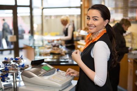 가게의 금전 등록기에서 일하는 판매원