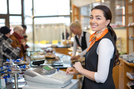 Shopkeeper and saleswoman at cash register or checkout counter Standard-Bild