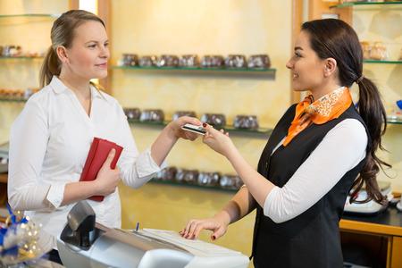 Client bei Shop Bezahlen an Kassen mit Verkäuferin Lizenzfreie Bilder
