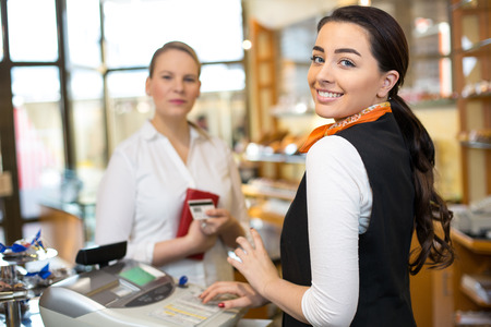saleswomen: Client at shop paying at cash register with saleswoman