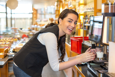 Waitress in caf� or restaurant at coffee machine photo