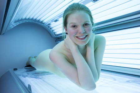 naked woman relaxing on tanning bed in solarium photo
