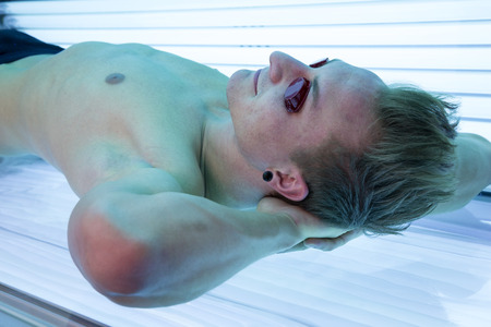 sunbed: Man with sunglasses on tanning bed in solarium Stock Photo