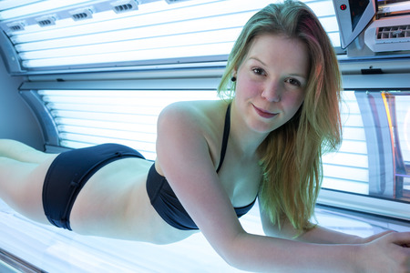 Customer or client in a solarium on tanning bed Stock Photo