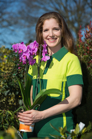 Florist or gardener posing with orchid flower photo