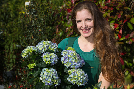 woman posing with hydrangea flower in nursery photo
