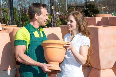 Employee in garden center selling pottery to customer or client photo