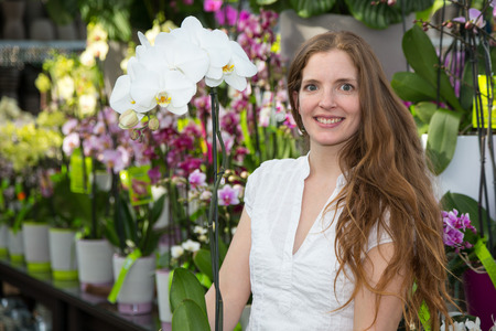 Customer in flower shop posing with an orchid photo