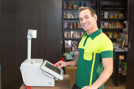 Cashier at cash register in shop or store with books in background photo
