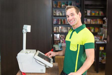 Cassiere al registratore di cassa in negozio o negozio con libri in background