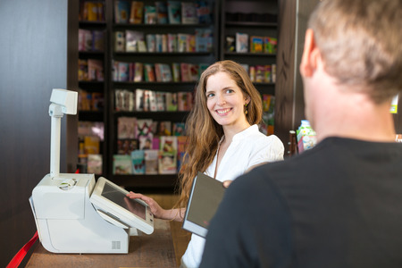 desk clerk: Female cashier in bookstore serving a customer or client