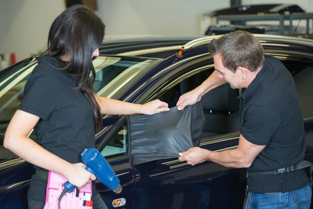 Team of car wrapping specialists wrapping side mirror with carbon foil